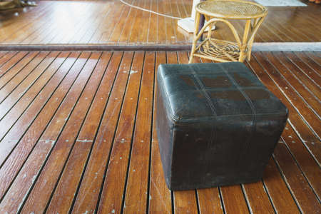 Leather stool chair, which has been used for a long time on wooden floors.