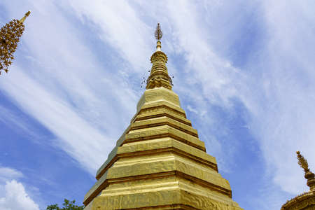 The top of the pagoda at Wat Phrathatchohae with blue sky background in Phrae province, Thailand