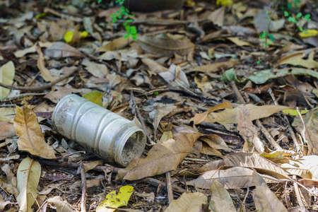 An old plastic jar was left in the garden with fallen leaves. Reklamní fotografie