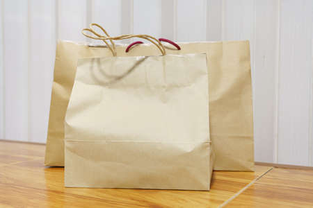Two sizes of paper shopping bags are placed on the floor.