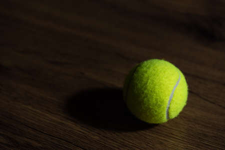Light and shadow style photo of a tennis ball on the wooden floor. Reklamní fotografie