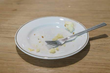 Fork and cake crumbs on the plate after eating the cake. Reklamní fotografie