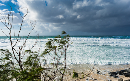 The stormy weather in summer day with cumulus grey clouds on the wild beach in Gold Coast, Australia