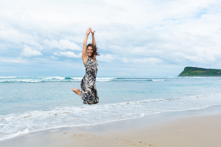 The young woman with happy face and long brown hair wearing long dress is jumping on the beach in gray morning with stormy clouds sky in Byron Bay, Australia Stock Photo
