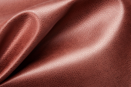 Brown eco leather. Artificial leather. Synthetic leather. Leatherette background.