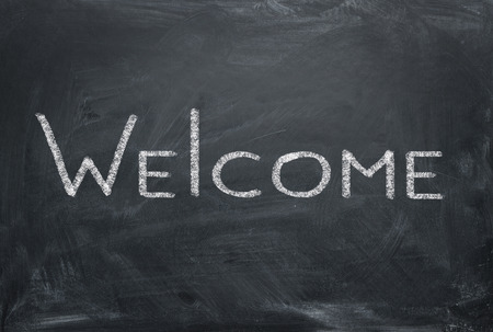 Welcome - inscription in chalk on a blackboard. Hospitality concept.