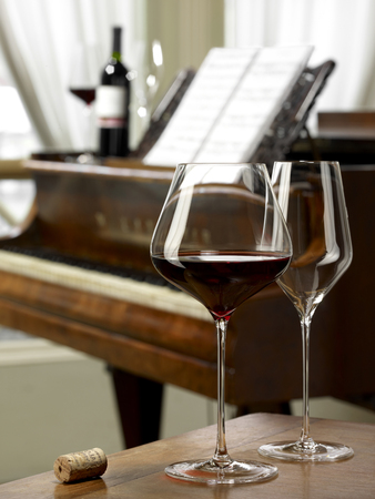 One glass of red wine and one empty wine glass on the table on grand piano background with bottle of wine.