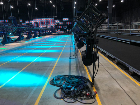 Installation of professional sound, light, video and stage equipment for a concert. Stage lighting equipment with power cables is clamped on a truss for lifting on led screen background.  Archivio Fotografico