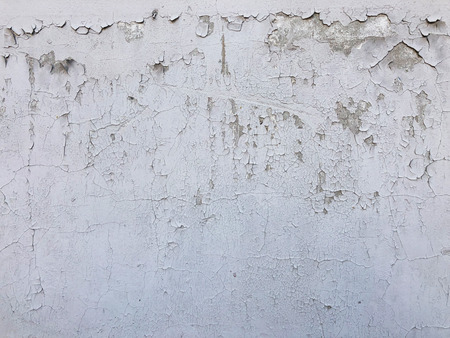 Old grey concrete wall with cracked and peeling paint.