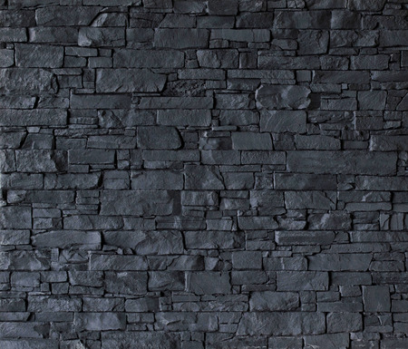 Black stone wall with rough surface texture background.