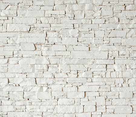 White stone wall with rough surface texture background. Banco de Imagens