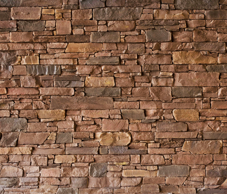 Brown stone wall with rough surface texture background.