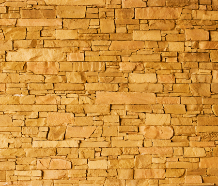 Yellow stone wall with rough surface texture background.