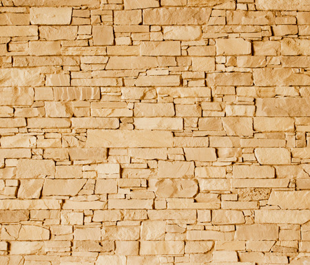 Light brown stone wall with rough surface texture background.