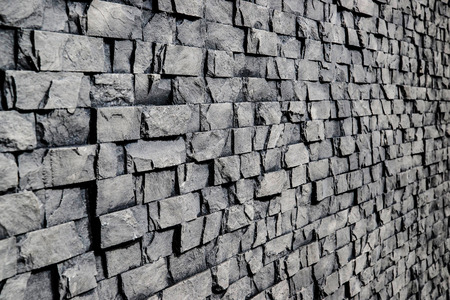 Grey stone wall with rough surface texture background. Angle view.