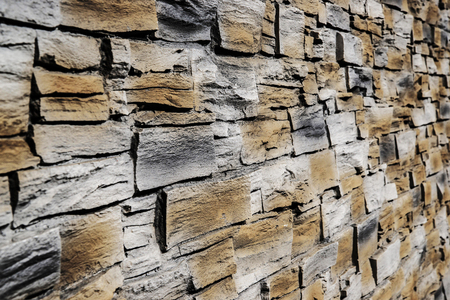 Grey and brown stone panel wall with rough surface texture background. Angle view. Imagens