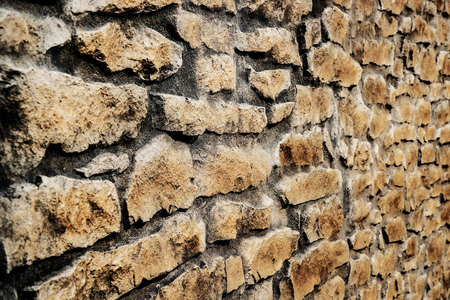 Brown stone panel wall with rough surface texture background. Angle view.