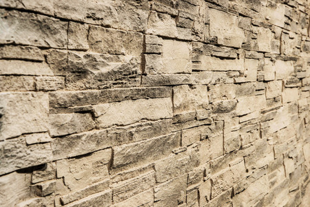 Light brown stone panel wall with rough surface texture background. Angle view. Imagens