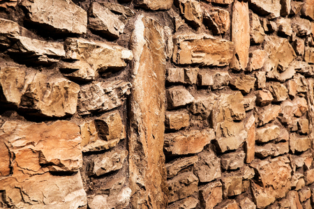 Brown rustic stone panel wall with rough surface texture background. Angle view. Imagens