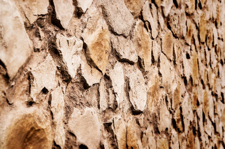 Brown rustic stone wall with rough surface texture background. Angle view.