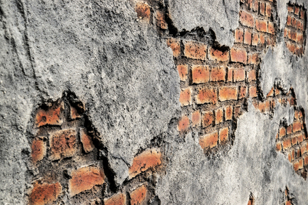 Rustic red brick wall with peeling cement texture background. Angle view.