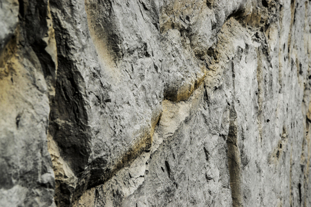 Closeup grey stone wall texture background. Angle view.