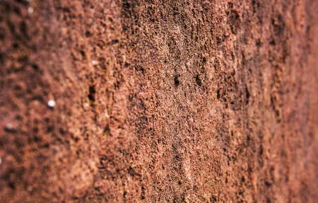 Closeup red stone wall texture background. Angle view.