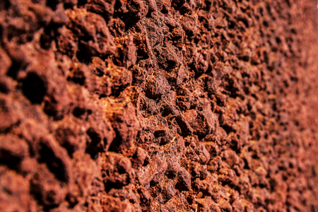 Closeup red rustic stone wall texture background. Angle view.