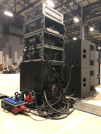 Installation of professional sound equipment for a concert. Racks with amplifiers, subwoofer speakers and electric power distribution boxes with signal cabels. Imagens - 121741701