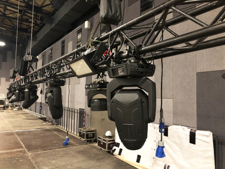 Spot lighting equipment is clamped on a truss for lifting. Installation of professional stage light equipment for a concert. Imagens - 121741702