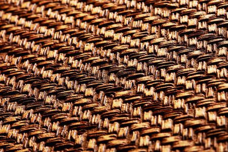 Gold bronze metal surface with abstract pattern texture background. Looks like wicker basket. Angle view. Imagens