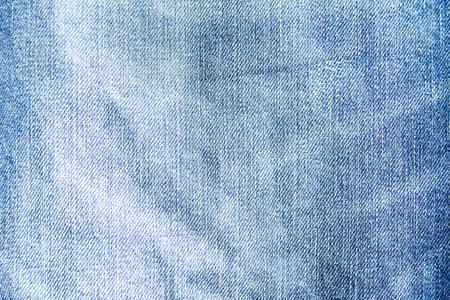 Crumpled blue jeans denim textile texture background.