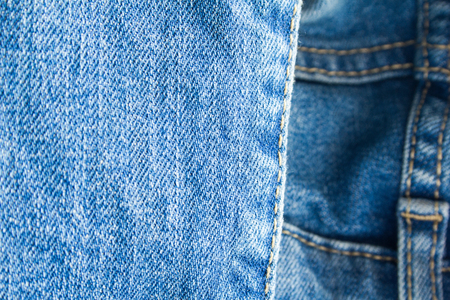 Blue jeans denim textile with seam texture background.