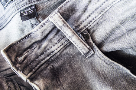 Closeup grey jeans with seams, pocket and size sticker texture background. Imagens