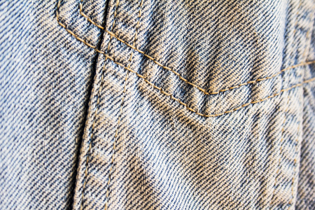 Closeup blue jeans denim textile with seam. Jeans fabric texture background with selective focus. Imagens