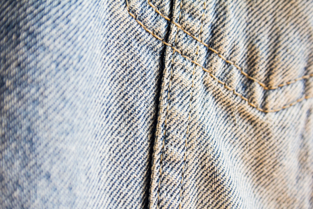 Closeup blue jeans denim fabric with seam. Jeans fabric texture background with selective focus. Imagens