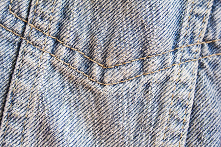 Closeup classic blue jeans denim fabric with seam texture background.