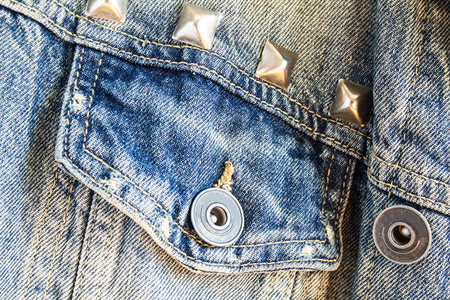 Closeup blue jeans denim fabric with seam, pocket, metal rivets and buttons.