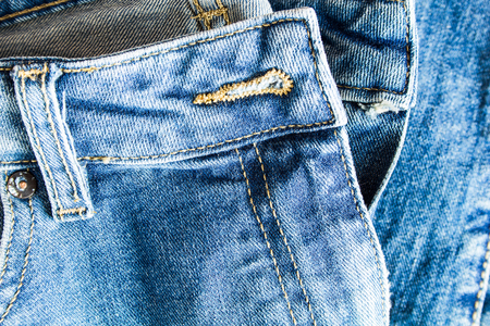Classic blue jeans denim fabric texture with seams.