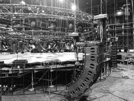 Installazione di attrezzature da concerto professionali. Sollevamento dei diffusori line array. Traliccio con apparecchi di illuminazione spot sopra il palco.