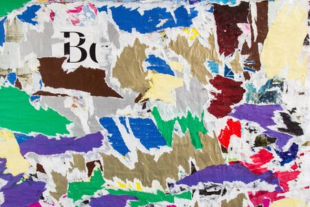 Colorful pieces of old torn and peeling paper posters and placards with dirty glue stains on billboard texture background.