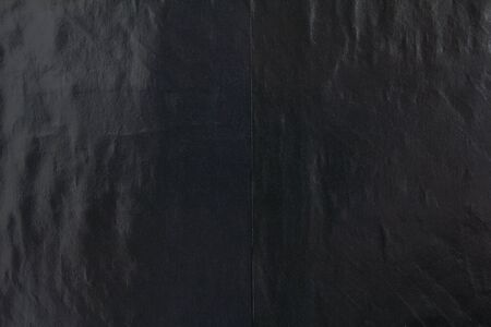 Black gloss wavy paper posters glued on billboard with rough surface texture background. Imagens