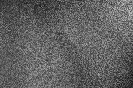 Closeup black eco leather texture background. Dark grey artificial synthetic leather.