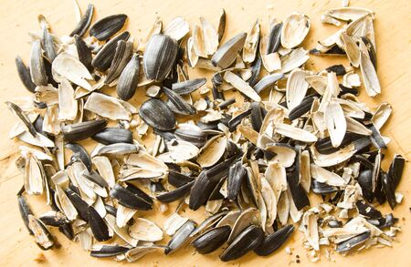 Closeup pile of peels from sunflower seeds on wooden table background. Banco de Imagens