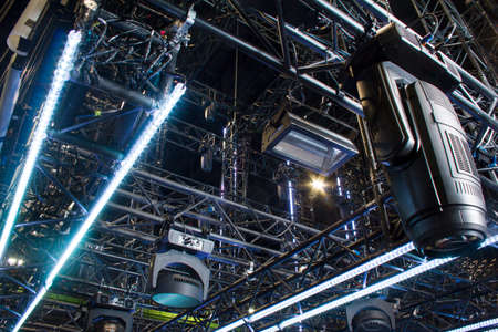 Moving heads spotlight devices are clamped on a rigging steel truss. Installation of professional stage light equipment for a concert show. Archivio Fotografico