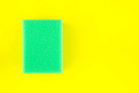 Green soft sponge or scouring pads for washing and cleaning on yellow background.