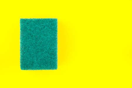 Green sponge or scouring pads with rough surface for washing and cleaning on yellow background.