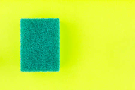 Green sponge or scouring pads with rough surface for washing and cleaning on green background.
