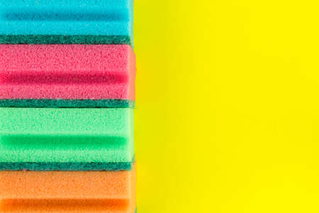 Colorful soft sponges or scouring pads for washing and cleaning on yellow background. Copy space for text.