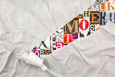 Torn and peeling gray paper on colorful collage from clippings with letters and numbers background.